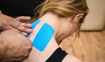 kinesiologist taping womans neck